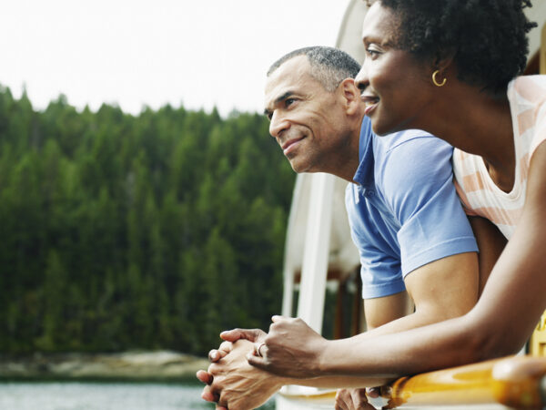 Mature couple on deck of yacht looking at view, smiling