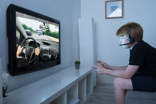 Boy With Joystick Playing Car Game On Television At Home