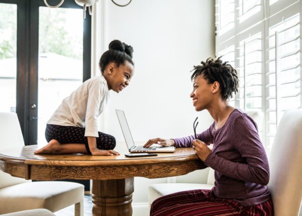 Mother working on laptop, daughter on table