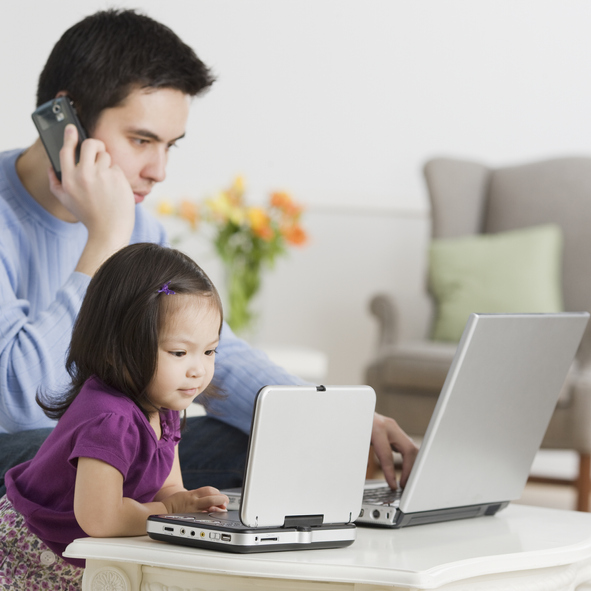Father and daughter using laptops