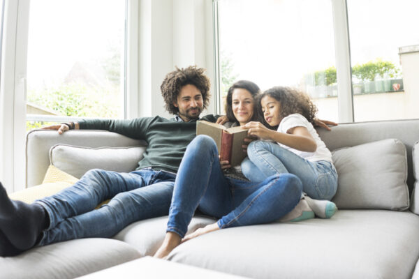 Happy family sitting on couch, reading book