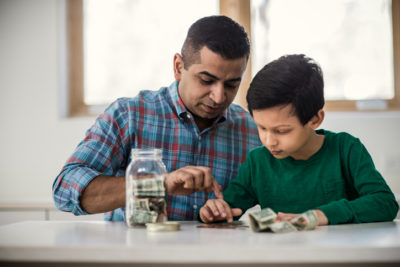 Father and son counting money at home