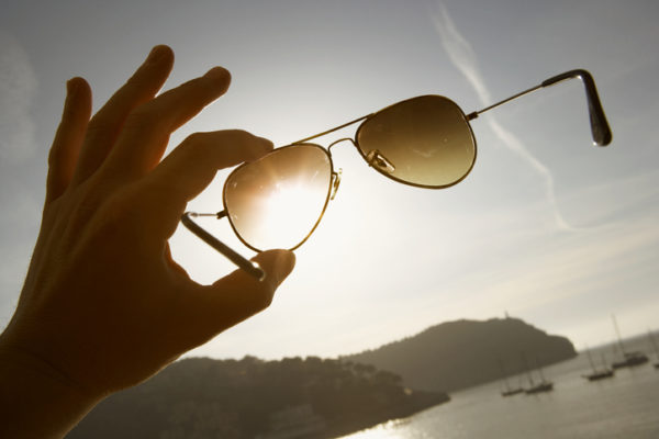 hand holding aviator sunglasses up against the sky