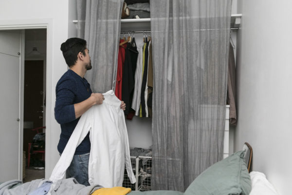 Side view of young man arranging clothes in closet at bedroom
