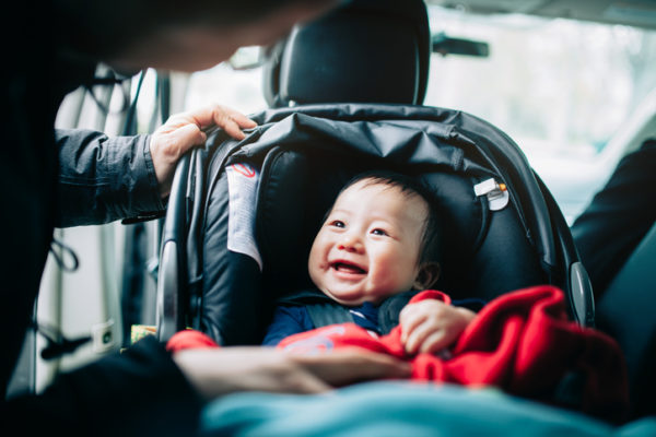 Close up of mother taking care of cute smiling baby on car seat in car