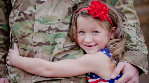 young girl hugs father for Military Appreciation Month