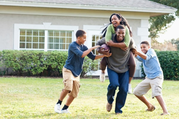 african-american family playing football in backyard