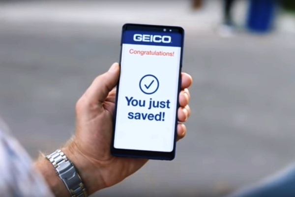 "hand holding phone showing GEICO ""You just saved!"""