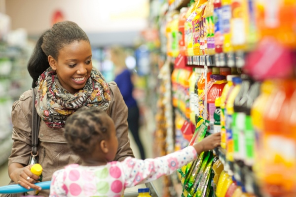 young mom shopping with daughter at grocery store