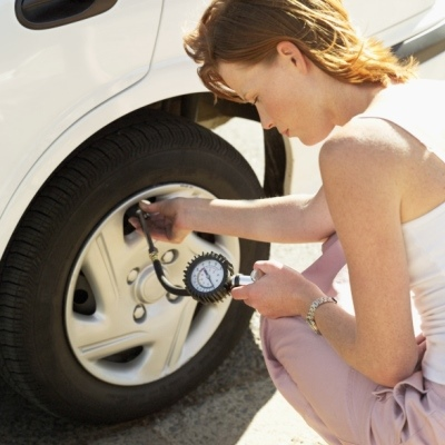 high angle view of a young woman checking the air pressure of a car tire