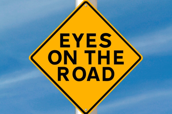 eyes on the road street sign