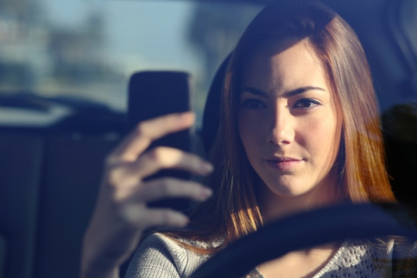 Front view of woman driving and typing on smart phone