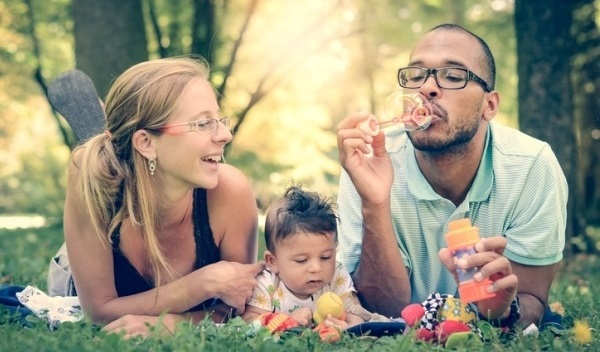 multi-racial family blowing bubbles in park
