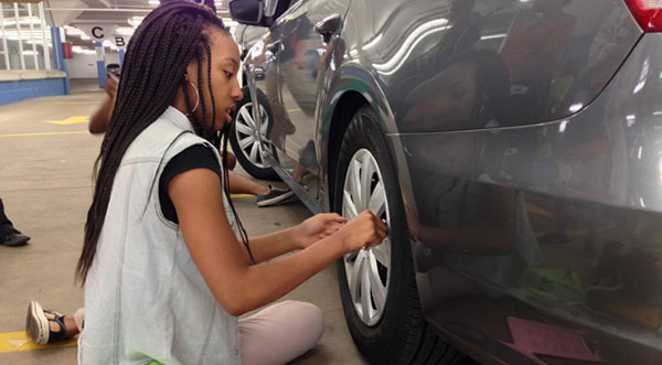 Girl Scout changing a tire
