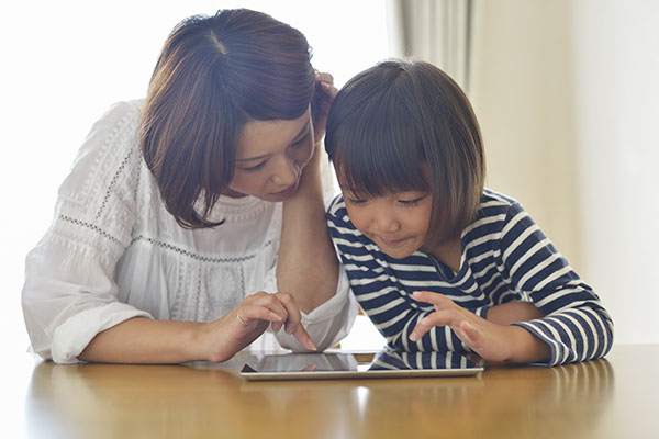 Mother and daughter working on tablet