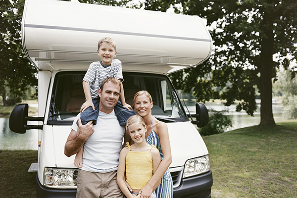 Family posing in front of RV camper