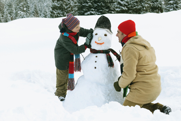 Father and son build a snowman