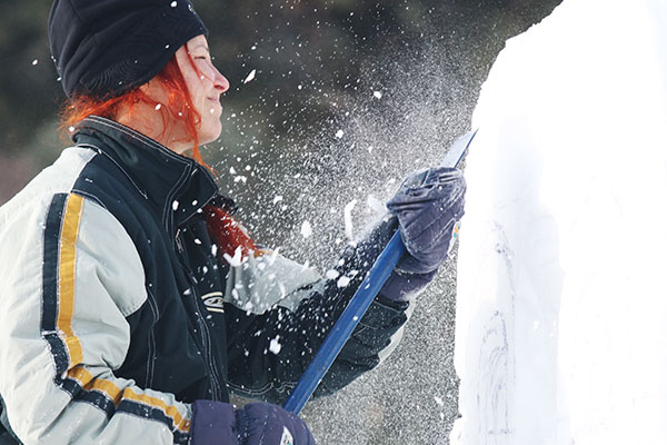 Young woman easily creating a snow sculpture
