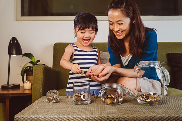 Asian mother and young daughter counting coins