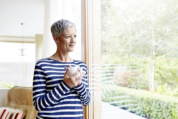 Older woman looking out window holding coffee mug
