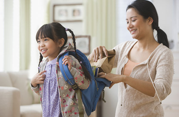 Mom packing child's backpack for school