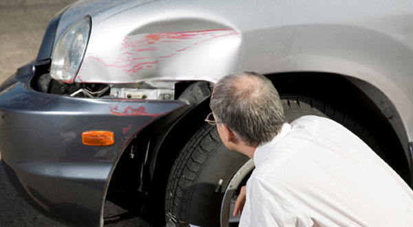 Insurance adjuster inspecting a vehicle's damage