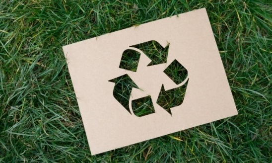 Recycle sign paper on grass