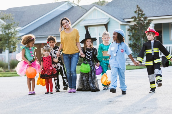 woman with group of children in halloween costumes