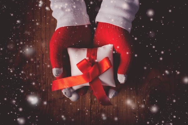 gloved hands holding out wrapped christmas gift