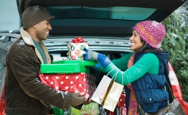 couple loading holiday gifts into car