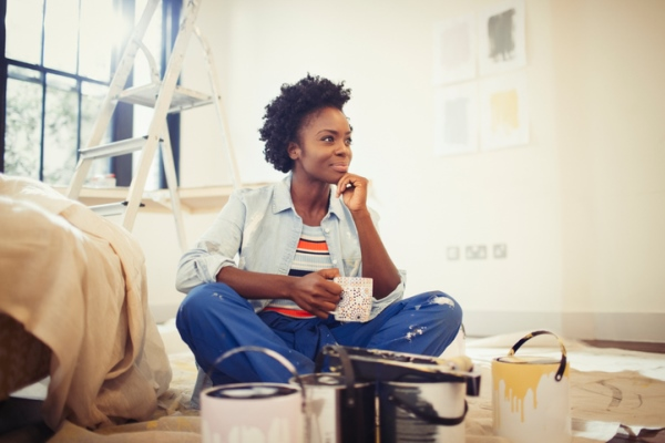 Satisfied woman drinking coffee and painting living room