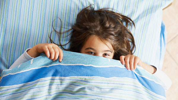 kid hiding under the covers in a bed