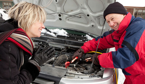 Two friends helping to jump start a car