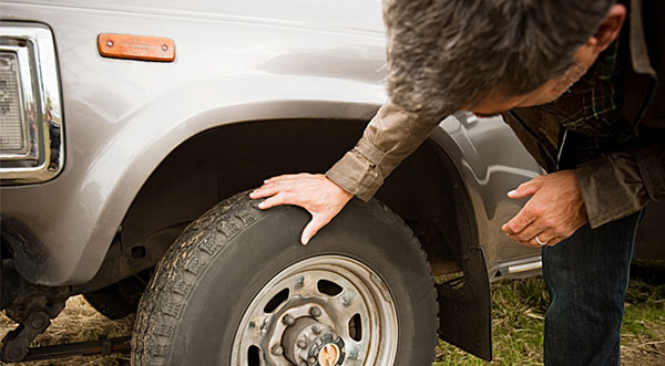 Checking a car's tires for wear and tear