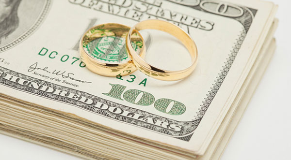 Wedding rings on stack of money