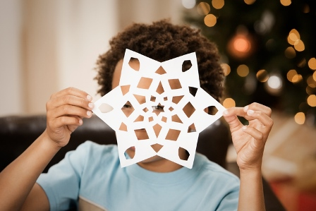 boy holding up paper snowflake