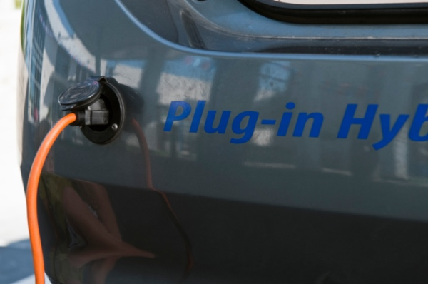 Close up of electrical plug recharging electric car