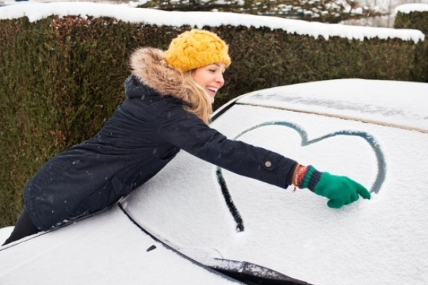 young woman drawing heart in show on car windshield