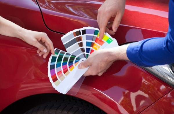 Mechanic Showing Color Samples To Customer Against Car