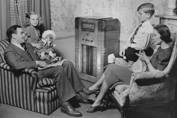 1950s family sitting around a radio