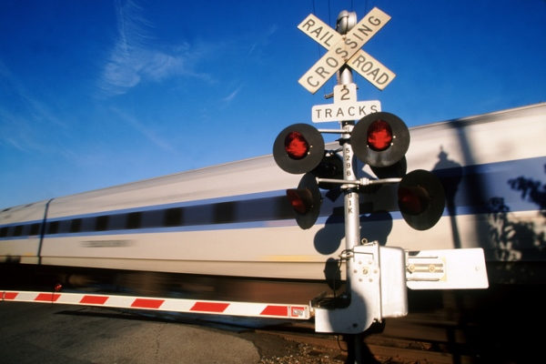 train speeding through railroad crossing