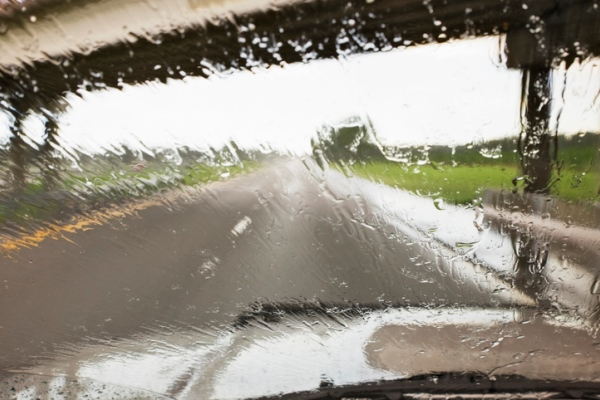 Raindrops on windshield driving on highway