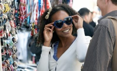 woman shopping for sunglasses at street vendor