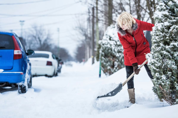 woman shoveling snow by the road