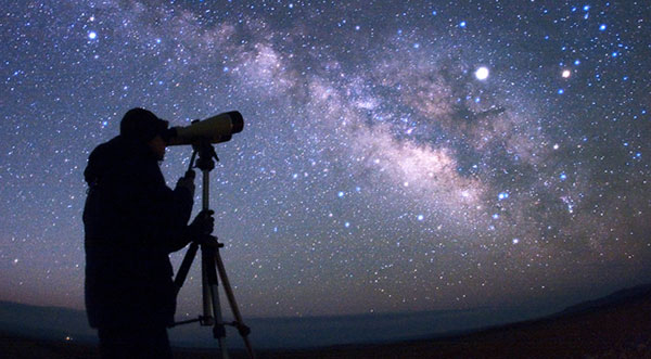 man star gazing with telescope