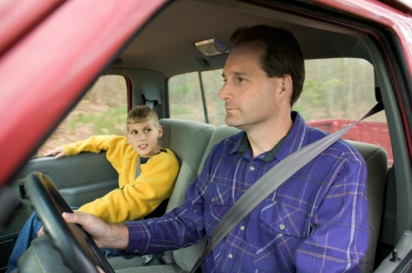 A boy looks at his father while he drives the truck.