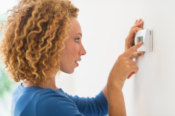 young woman programming a thermostat