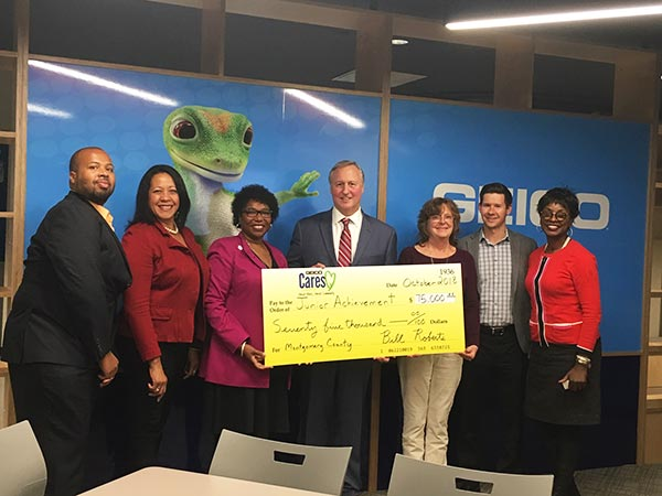 GEICO associates pose for a check presentation in the new Junior Achievement Finance Park room