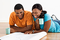 man and woman drinking coffee and reviewing blueprints