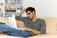man sitting on a couch using a laptop